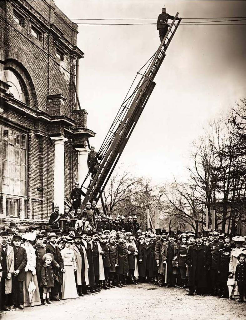 Группа членов Санкт-Петербурского Пригородного Пожарного Общества в день празднования 5-ти летнего юбилея у здания Народного дома. 1903 г.